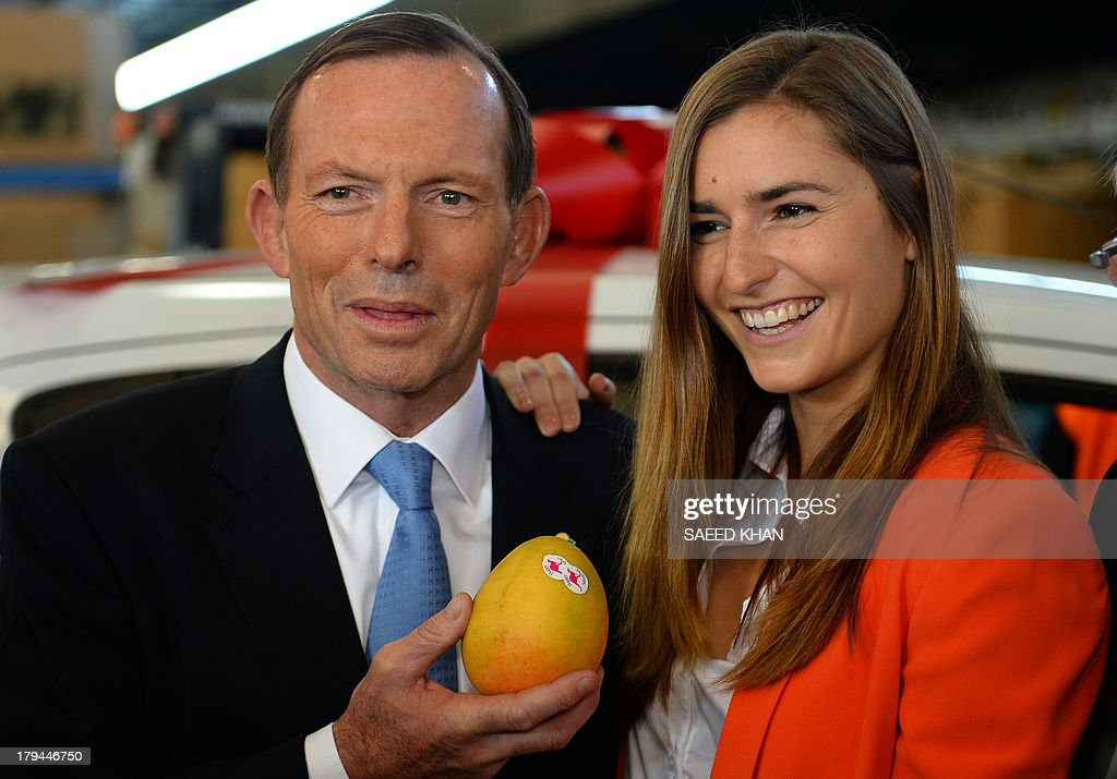 Australian opposition leader Tony Abbott holds a mango while posing for pictures with his daughter during a tour of the Sydney market at Flemington on September 4, 2013. Election campaign in Australia is on its peak ahead of poll on September 7, 2013. AFP PHOTO / Saeed KHAN