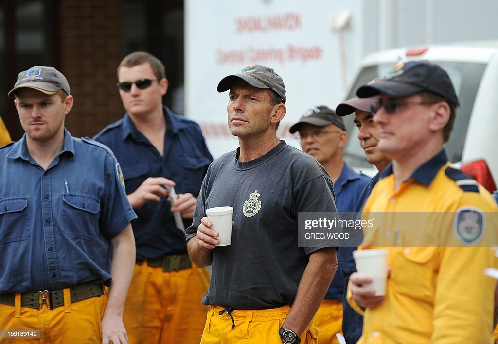 Australian opposition leader Tony Abbott (C) listens to a bushfire briefing as he prepares to help in his capacity as a member of the rural fire service at the incident control centre at Nowra on the south coast of Australia's New South Wales state on January 9, 2013. Cooler conditions helped firefighters battling blazes across Australia on January 9 but up to 30 were still out of control, destroying a handful of homes and killing thousands of livestock. AFP PHOTO / Greg WOOD
