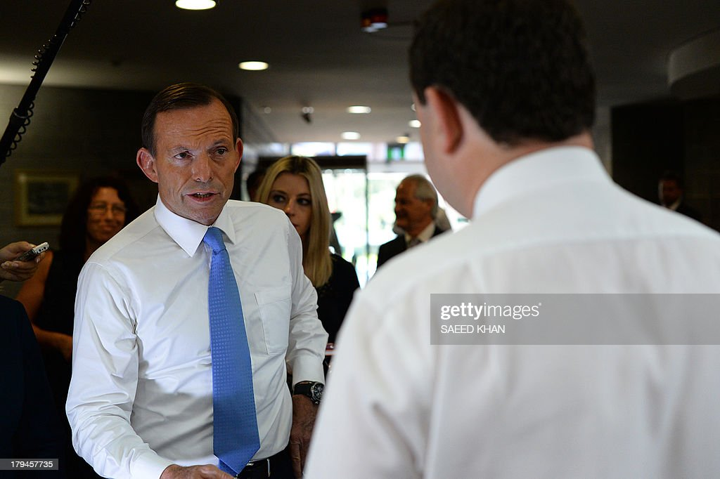 Australian opposition leader Tony Abbott (L) listens to an official about future road plans at the Penrith city council in Sydney on September 4, 2013. Australian election frontrunner Tony Abbott vowed Asia will be his main foreign policy focus if he assumes office, as an influential media group turned on incumbent Prime Minister Kevin Rudd. AFP PHOTO / Saeed KHAN