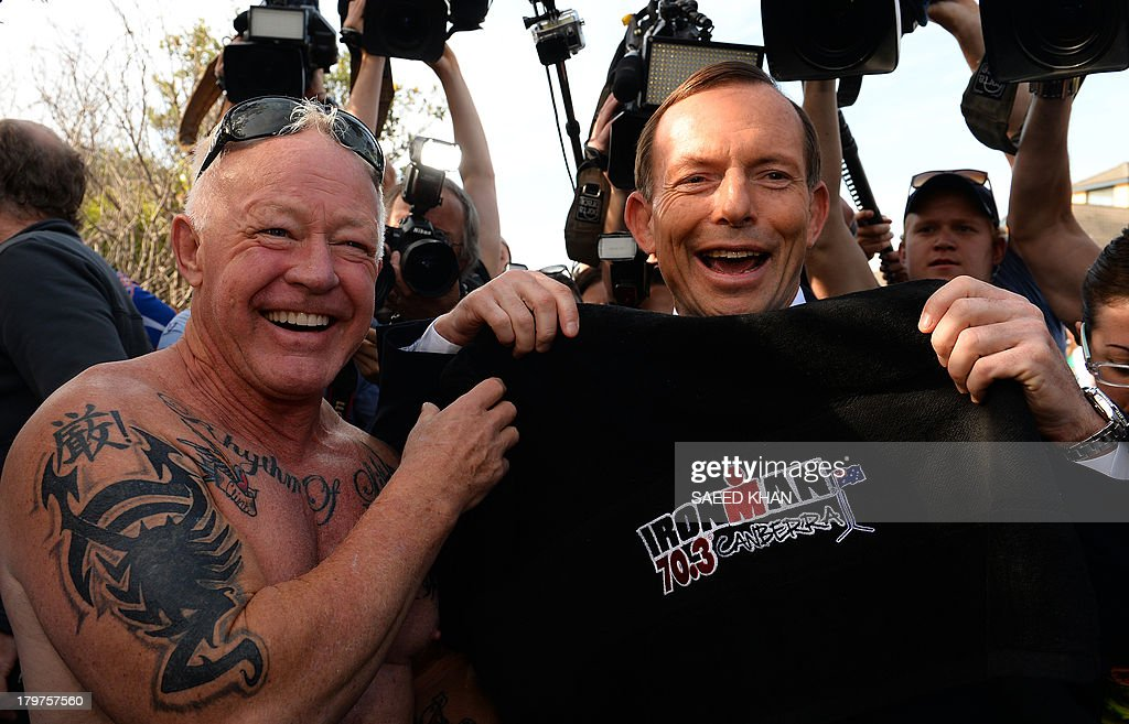 Australian opposition leader Tony Abbott (R) shares a light moment with a tattooed voter outside a polling station in Sydney on September 7, 2013. Australians began voting in national elections with conservative challenger Tony Abbott heading for a thumping victory over Labor Prime Minister Kevin Rudd. AFP PHOTO / Saeed KHAN