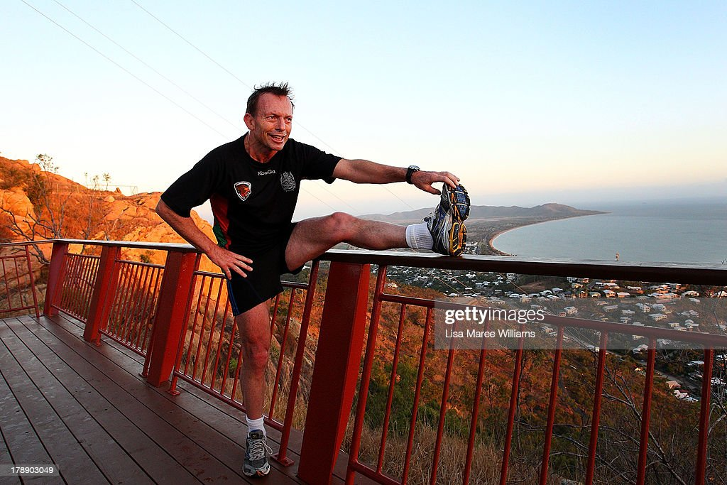 Australian Opposition Leader <a gi-track='captionPersonalityLinkClicked' href=/galleries/search?phrase=Tony+Abbott&family=editorial&specificpeople=220956 ng-click='$event.stopPropagation()'>Tony Abbott</a> stretches his legs after running up Castle Hill with security staff on August 31, 2013 in Townsville, Australia. Australian voters will head to the polls on September 7 to elect the 44th parliament.