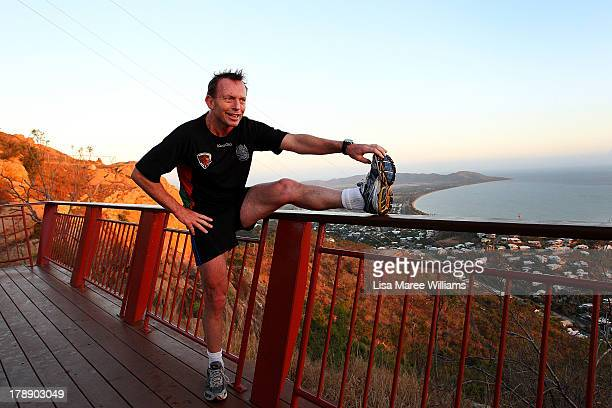 Australian Opposition Leader Tony Abbott stretches his legs after running up Castle Hill with security staff on August 31 2013 in Townsville...