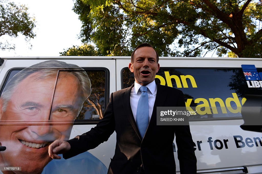 Australian opposition leader Tony Abbott walks in front of one of his party candidate's election campaign vans in Sydney on August 19, 2013. Australia's embattled Labor Prime Minister Kevin Rudd warned the country faced the risk of a recession if the conservative opposition are elected at next month's polls. AFP PHOTO / Saeed KHAN