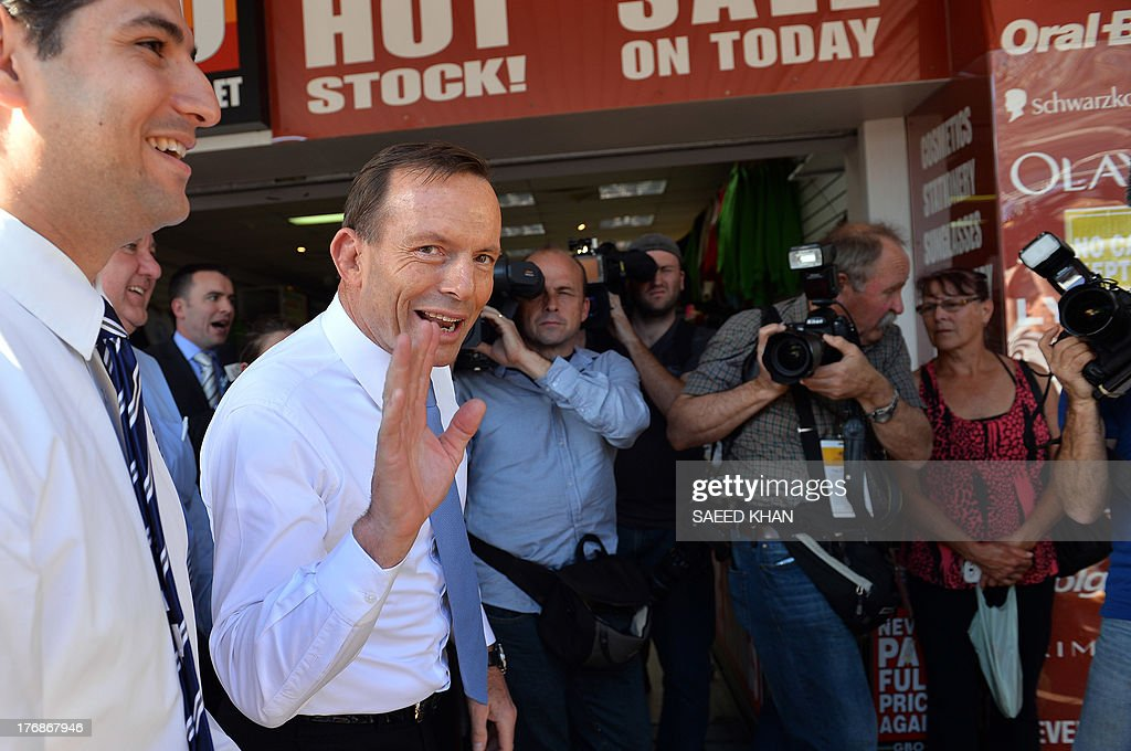 Australian opposition leader Tony Abbott (C) waves to shoppers during a street walk in the Liverpool suburbs of Sydney on August 19, 2013. A defiant Australian Prime Minister Kevin Rudd warned not to write him off as a new poll showed his popularity slumping barely three weeks away from elections. After a fortnight of relentless campaigning, a Newspoll for The Australian newspaper showed voter satisfaction with him at 35 percent, down four points, while conservative rival Tony Abbott saw a three-point jump to 41 percent. AFP PHOTO / Saeed KHAN