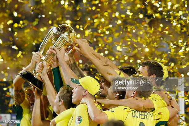 Australian players celebrate with the tophy after the 2015 ICC Cricket World Cup final match between Australia and New Zealand at Melbourne Cricket...