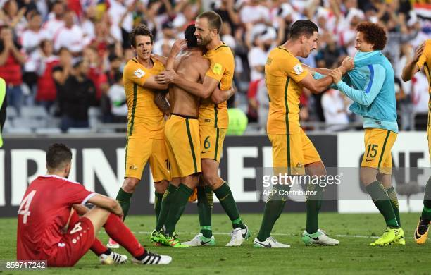 TOPSHOT Australian players celebrates after they defeated Syria in their 2018 World Cup football qualifying match played in Sydney on October 10 2017...