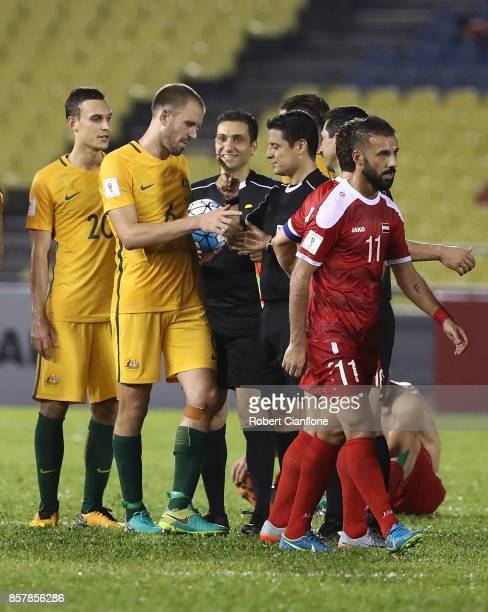 Australian players talk to referee Alireza Faghani after the 2018 FIFA World Cup Asian Playoff match between Syria and the Australia Socceroos at...