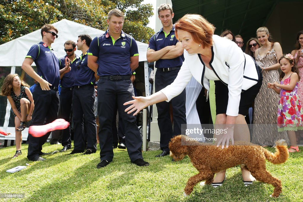 Australian players watch Australian Prime Minister, Julia Gillard throw a soft toy for her dog 'Reuben' during a function at Kirribilli House on January 1, 2013 in Sydney, Australia.
