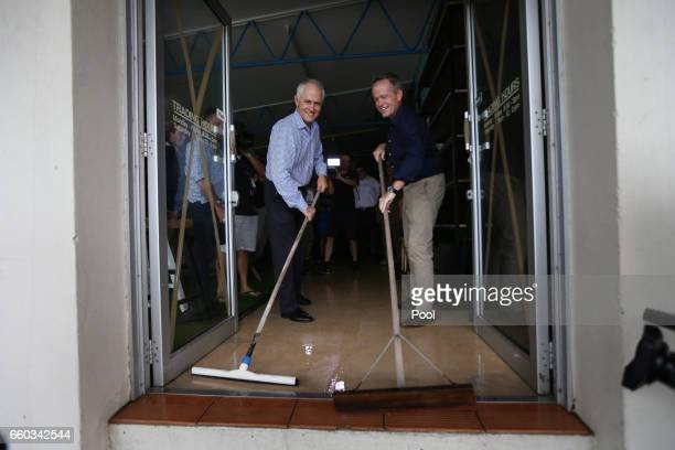 Australian PM Malcolm Turnbull and Opposition Leader Bill Shorten sweep water from a store in a cyclone damaged area March 30 2017 in Bowen Australia