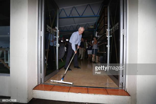 Australian PM Malcolm Turnbull sweeps water from a store in a cyclone damaged area March 30 2017 in Bowen Australia