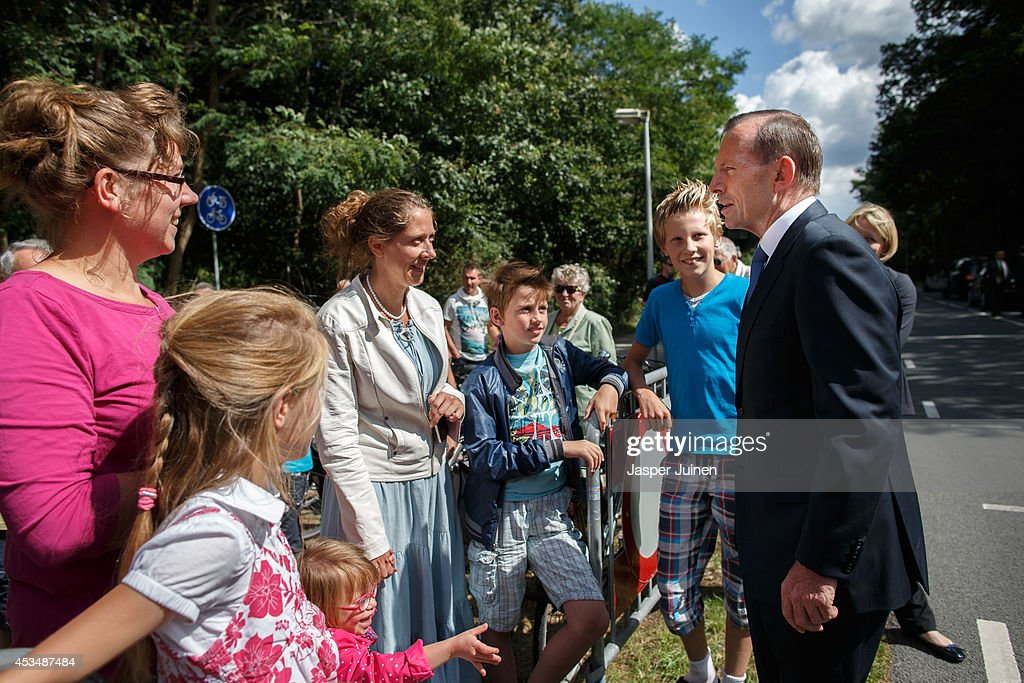 Australian PM Tony Abbott speaks with bystanders of whom some came to lay flowers after laying a wreath in remembrance of the victims of Malaysia...