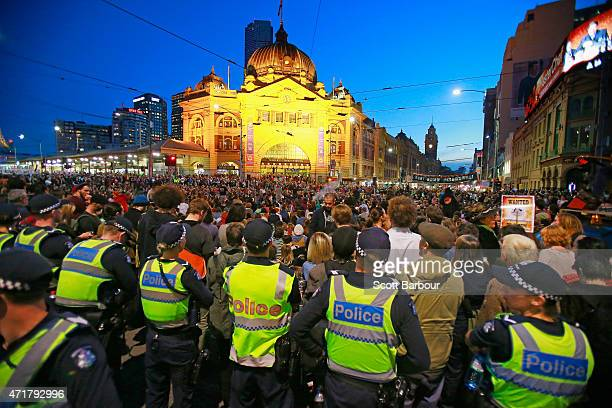 Australian Police Officers look on as protesters stage a sit down protest outside of Flinders Street Station on May 1 2015 in Melbourne Australia...