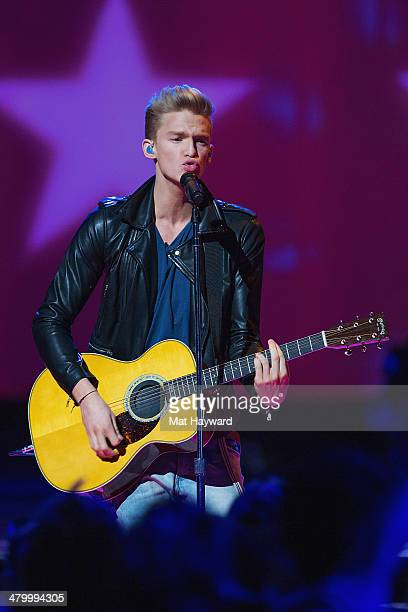 Australian pop singer and awardwinning musician Cody Simpson performs on stage during We Day at Key Arena on March 21 2014 in Seattle Washington