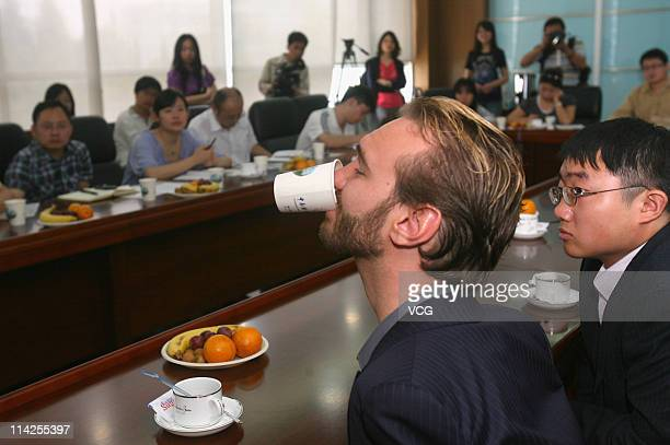 Australian preacher and motivational speaker Nick Vujicic drinks water by himself at a press conference prior to his public lecture at Zhongnan...