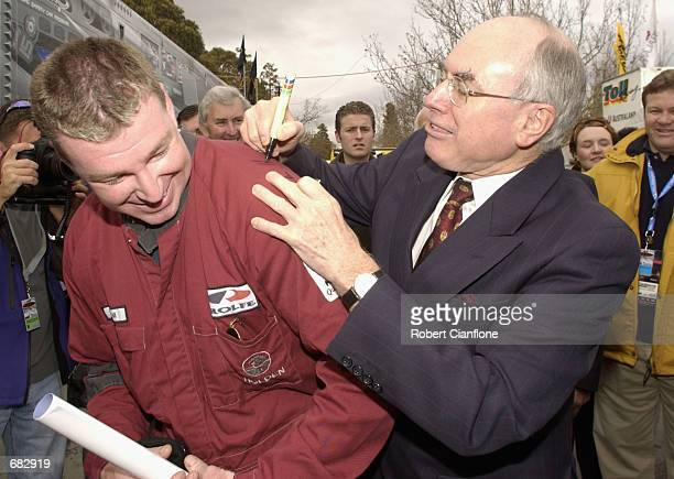 Australian Prime Minister John Howard signs the overall of a mechanic during the Stegbar Canberra 400 which is round 5 of the Shell Championship...