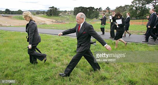 Australian Prime Minister John Howard strides across the boggy ground with his finance minister Peter Costello after a press conference committing...