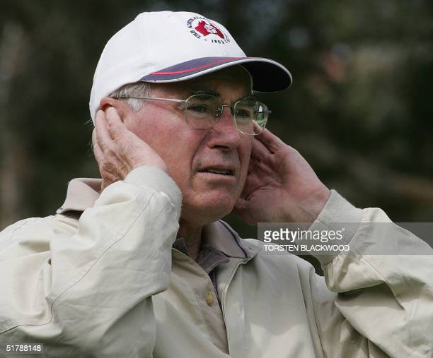 Australian Prime Minister John Howard watches American golfing icon Arnold Palmer Australian greats Bruce Devlin and Peter Thomson playing a ninehole...