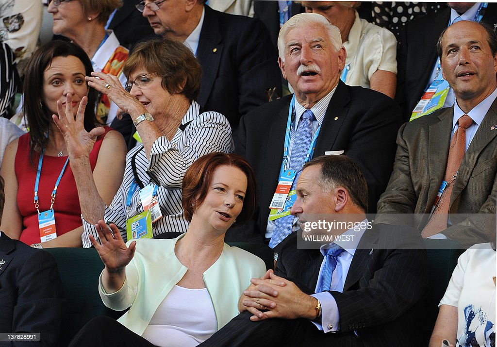 Australian Prime Minister Julia Gillard (C) and New Zealand Prime Minister John Key (R) speak as they sit with dignitaries including former tennis champion Margaret Court (2L) as they prepare to watch Maria Sharapova of Russia during her women's singles final against Victoria Azarenka of Belarus on the thirteenth day of the Australian Open tennis tournament in Melbourne on January 28, 2012. IMAGE