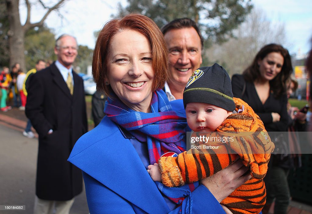 Australian Prime Minister <a gi-track='captionPersonalityLinkClicked' href=/galleries/search?phrase=Julia+Gillard&family=editorial&specificpeople=787281 ng-click='$event.stopPropagation()'>Julia Gillard</a> is watched by her partner Tim Mathieson as she holds a baby dressed in the colours of the Richmond Tigers as they make their way to an Australian Rules football game after launching the Korin Gamadji Institute at the ME Bank Centre on August 12, 2012 in Melbourne, Australia.