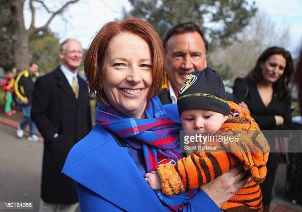 Australian Prime Minister Julia Gillard is watched by her partner Tim Mathieson as she holds a baby dressed in the colours of the Richmond Tigers as...