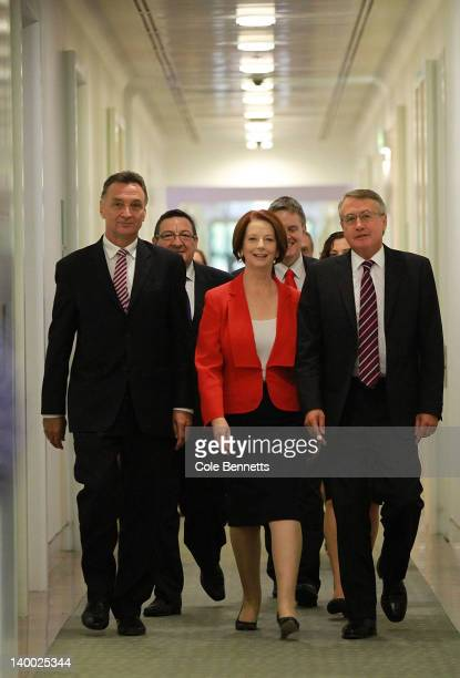 Australian Prime Minister Julia Gillard leaves with federal treasurer Wayne Swan and Trade minister Craig Emerson after the caucus meeting on...