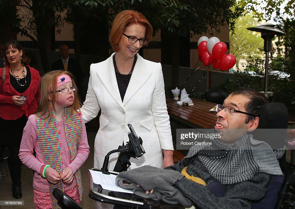 Australian Prime Minister Julia Gillard meets Sophie Dean (L) and Dr George Taleporos (R) from the disabled community after a press conference at the Commonwealth Parliamentary Office on May 1, 2013 in Melbourne, Australia. Gillard has announced that the Federal Government will increase the Medicare levy on income tax from 1.5 to two percent to help fund the National Disability Insurance Scheme (NDIS). The levy will begin on July 1, 2014 and is expected to raise around $3.2 billion annually towards the NDIS which is expected to cost $8 billion per year.