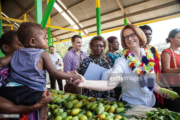 Australian Prime Minister Julia Gillard shakes hands with the child of a market seller in Gerehu market in Port Moresby during her trip to Papua New...