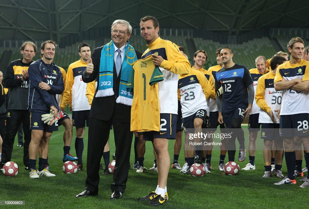 Australian Prime Minister Kevin Rudd is handed a Socceroos shirt by Australian captain Lucas Neill and prior to an Australian Socceroos training session at AAMI Park on May 20, 2010 in Melbourne, Australia.