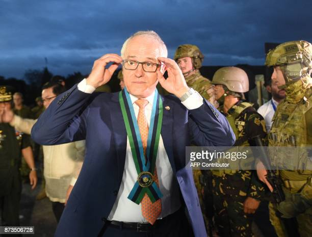 Australian Prime Minister Malcolm Turnbull adjusts his glasses as he speaks with members of the media during a visit to the military headquarters in...