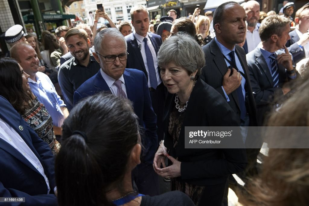 Australian Prime Minister, Malcolm Turnbull (centre left) and Britain's Prime Minister Theresa May (C) speak to market traders during a visit to Borough Market in central London on July 10, 2017, the scene of the June 3 terror attack. Seven people were killed, two of them Australian, in a terror attack in the British capital on June 3, 2017, when a van smashed into pedestrians on London Bridge before three assailants went on a stabbing spree. / AFP PHOTO / POOL / Niklas HALLEN