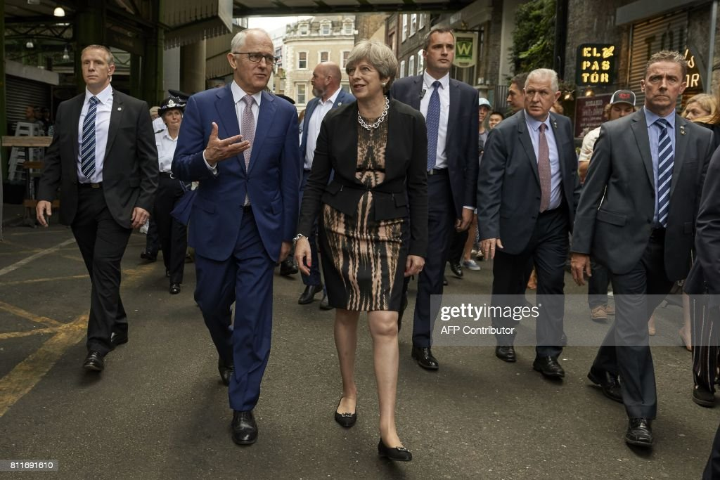 Australian Prime Minister, Malcolm Turnbull (2nd L) and Britain's Prime Minister Theresa May (C) tour Borough Market in central London on July 10, 2017, the scene of the June 3 terror attack. Seven people were killed, two of them Australian, in a terror attack in the British capital on June 3, 2017, when a van smashed into pedestrians on London Bridge before three assailants went on a stabbing spree. / AFP PHOTO / POOL / Niklas HALLEN