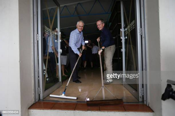 Australian Prime Minister Malcolm Turnbull and opposition leader Bill Shorten wipe flood waters out of a building as they visit areas of Bowen in...