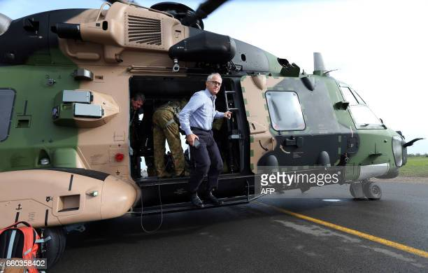 Australian Prime Minister Malcolm Turnbull comes out of a military helicopter as he visits an area of Bowen in northern Queensland damaged by Cyclone...