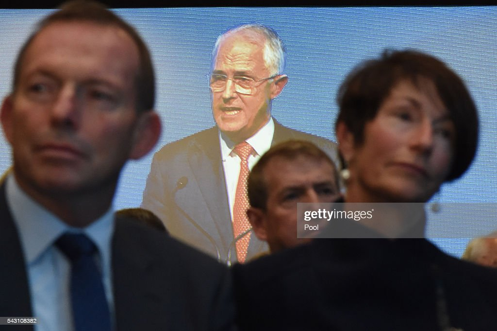 Australian Prime Minister Malcolm Turnbull is seen on a screen behind Former Australian Prime Minister Tony Abbott and his wife Margie as he addresses party members at the Coalition Campaign Launch in Sydney, Sunday, June 26, 2016. A federal election will be held in Australia on Saturday July 2.
