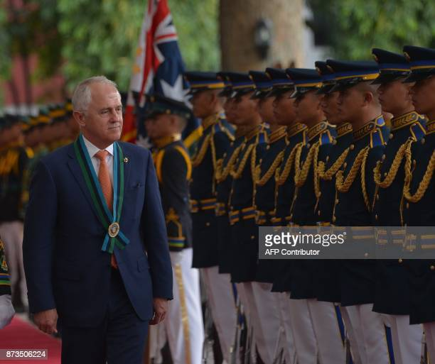 Australian Prime Minister Malcolm Turnbull reviews a honour guard during a visit to the military headquarters in Quezon City on November 13 on the...