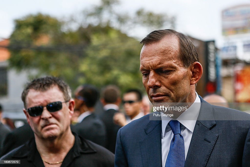 Australian Prime Minister Tony Abbott (R) and Bali Bombing victim, Peter Hughes talk with journalist at press conference on October 9, 2013 in Kuta, Indonesia. Mr Abbott has announced the Victims of Overseas Terrorism Compensation Scheme will now include attacks dating back to September 10, 2001.