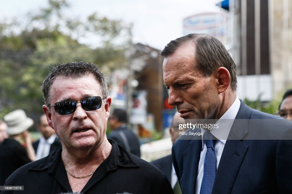 Australian Prime Minister <a gi-track='captionPersonalityLinkClicked' href=/galleries/search?phrase=Tony+Abbott&family=editorial&specificpeople=220956 ng-click='$event.stopPropagation()'>Tony Abbott</a> and Bali Bombing victim, Peter Hughes talk with journalist at press conference on October 9, 2013 in Kuta, Indonesia. Mr Abbott has announced the Victims of Overseas Terrorism Compensation Scheme will now include attacks dating back to September 10, 2001.