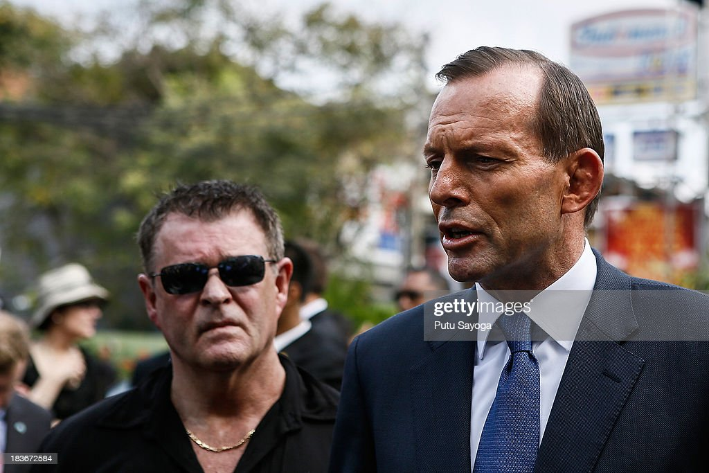 Australian Prime Minister <a gi-track='captionPersonalityLinkClicked' href=/galleries/search?phrase=Tony+Abbott&family=editorial&specificpeople=220956 ng-click='$event.stopPropagation()'>Tony Abbott</a> (R) and Bali Bombing victim, Peter Hughes (L) talk with journalist at press conference on October 9, 2013 in Kuta, Indonesia. Mr Abbott has announced the Victims of Overseas Terrorism Compensation Scheme will now include attacks dating back to September 10, 2001.