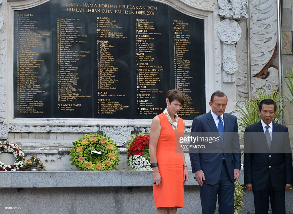 Australian Prime Minister Tony Abbott (C) and his spouse Margaret Aitken (L) accompanied by Bali Governor Mangku Pastika (R) visit the Bali bombing monument in Kuta, on October 9, 2013, before he leaves for Bali after attending the APEC 2013 meeting. The monument stands across from the old Sari Club that Islamists attacked, together with Paddy's Bar, on October 12, 2002, bringing carnage to Kuta's party strip. AFP PHOTO / Bay ISMOYO