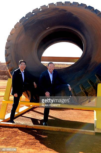 Australian Prime Minister Tony Abbott and Japanese Prime Minister Shinzo Abe pose for a photograph next to a haulage truck tyre during a tour of Rio...