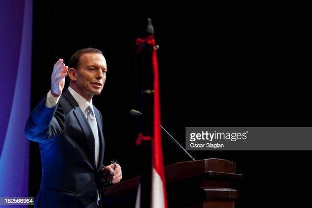 Australian Prime Minister Tony Abbott gestures as he delivers his speech during a business breakfast with Indonesian and Australian businessmen on...