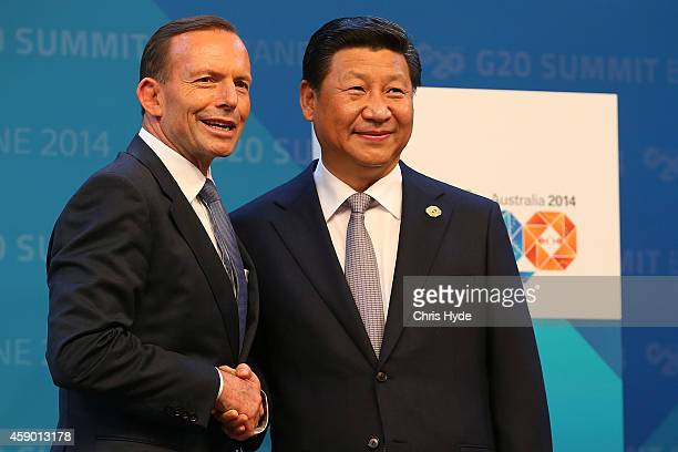 Australian Prime Minister Tony Abbott greets China's President Xi Jinping during the official welcome at the Brisbane Convention and Exhibitions...