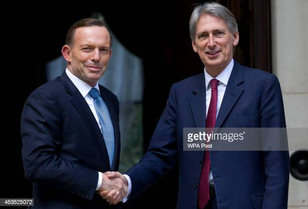 Australian Prime Minister Tony Abbott is greeted by British Foreign Minister Philip Hammond outside the Foreign Commonwealth Office on August 12 2014...
