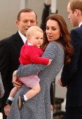 Australian Prime Minister Tony Abbott looks on as Catherine Duchess of Cambridge holds Prince George of Cambridge on April 25 2014 in Canberra...