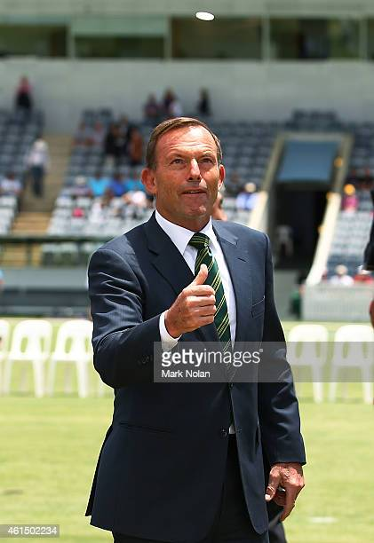 Australian Prime Minister Tony Abbott performs the coin toss with English captain Eoin Morgan and th PMs XI captain Chris Rogers before the tour...