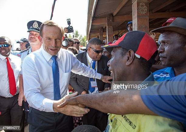 Australian Prime Minister Tony Abbott shakes hands with a local vendors during his tour of a market in Port Moresby on March 21 2014 Abbott arrived...