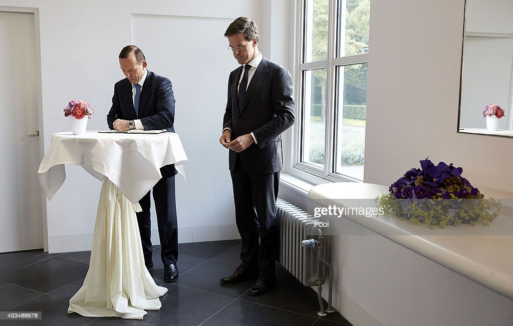 Australian Prime Minister Tony Abbott signs the book of condolence for the victims of Flight MH 17 beside Dutch Prime minister Mark Rutte at the...