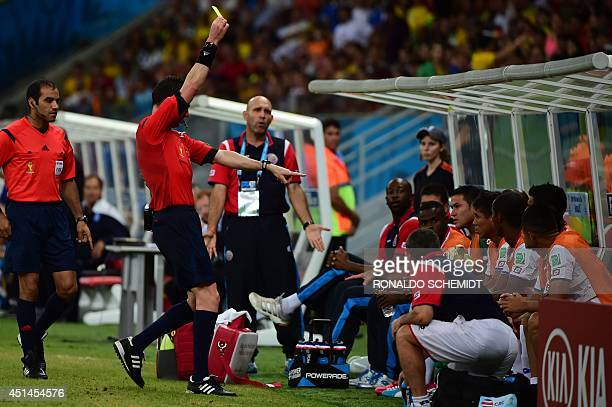 Australian referee Benjamin Williams shows a yellow card to Costa Rica's midfielder Oscar Esteban Granados sitting on the bench during the round of...