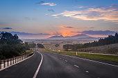 Australian road trip concept. Motion blur highway landscape at dusk with mountain Ararat in background. Victoria, Australia