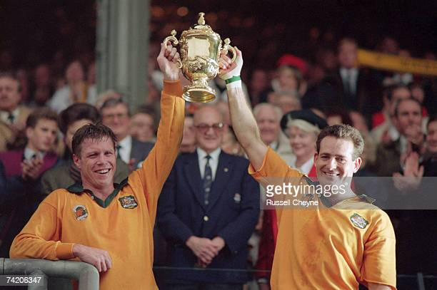 Australian scrumhalf Nick FarrJones and winger David Campese lift the Webb Ellis Cup after Australia's 126 victory over England in the Rugby World...